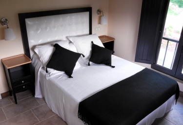 Bedroom with double bed and cushions on top